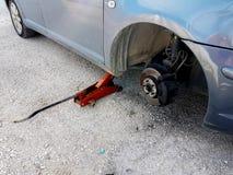 汽车泄了气的轮胎变动替换在路问题紧急状态 免版税图库摄影