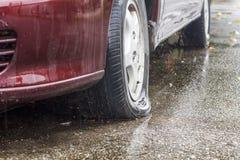 汽车泄了气的轮胎在雨天 免版税图库摄影
