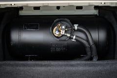 黑汽车液化石油气,与米关闭的LPG坦克 免版税库存图片