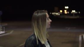 汽车燃料 站立在她的汽车附近的可爱的白种人妇女,当给它加油时 倾斜在汽车的白肤金发的妇女 夜间 影视素材