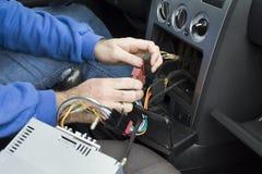 汽车电工的手连接从收音机的缆绳到汽车` s电气系统 免版税库存照片