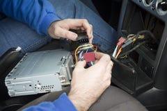 汽车电工的手连接收音机到汽车` s电气系统 免版税图库摄影