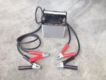 汽车电池修理有汽车电池充电器的在肮脏的parkin 库存照片