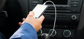 汽车电话的盘区和白色充电器在手中 免版税库存照片