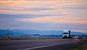 汽车的专栏用半在晚上弯曲道路的卡车带领了 库存照片