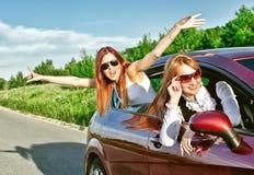 汽车的两个相当愉快的女孩。 免版税库存图片
