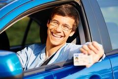 从汽车的人展示驾照 免版税库存图片