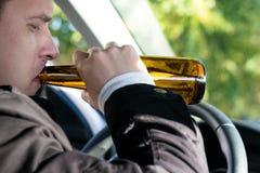 汽车的司机喝在轮子后的酒精饮料 免版税图库摄影