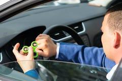 汽车的司机在轮子后在他的手上坐并且拿着一名锭床工人,镇定 库存照片