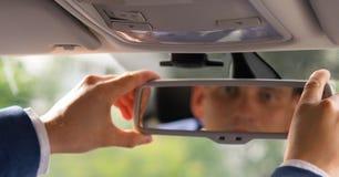 汽车的司机,在离开前调整镜子为路 图库摄影