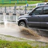 汽车的图象通过水坑飞溅在一个被充斥的街道特写镜头 免版税库存图片