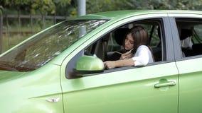 汽车的女孩谈话在关于事务的电话和做在笔记本的笔记 股票视频