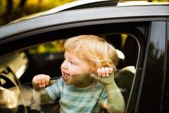 汽车的小男孩,看在窗口外面,挥动 库存图片
