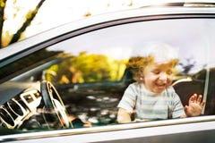 汽车的小男孩,看在窗口外面,挥动 免版税库存照片