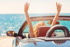 汽车的愉快和无忧无虑的妇女在海滩 库存图片