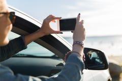 汽车的愉快的少妇有海上的智能手机的 免版税库存图片