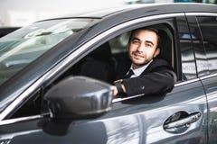 汽车的愉快的微笑的司机,年轻成功的商人画象  图库摄影