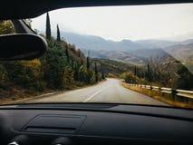 从汽车的看法通过一条山高速公路的挡风玻璃在克里米亚 免版税库存图片