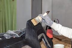 汽车的腰部的大师应用与一把刷子的胶浆在黏贴的皮革顶面塑料盘区在设计车间 库存图片