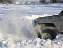 汽车的轮子在雪被困住 雪浪花从冬天转动的轮子的疲倦 滑倒在雪的机器 Th 免版税库存图片