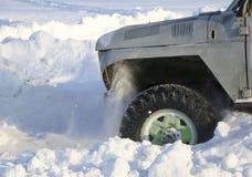 汽车的轮子在雪被困住 雪浪花从冬天转动的轮子的疲倦 滑倒在雪的机器 Th 免版税库存照片
