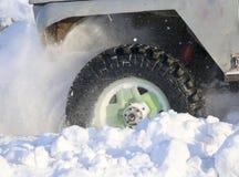 汽车的轮子在雪被困住 雪浪花从冬天转动的轮子的疲倦 滑倒在雪的机器 Th 库存图片