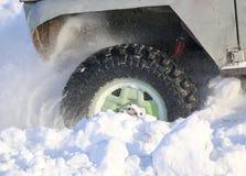 汽车的轮子在雪被困住 雪浪花从冬天转动的轮子的疲倦 滑倒在雪的机器 Th 免版税图库摄影