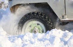 汽车的轮子在雪被困住 雪浪花从冬天转动的轮子的疲倦 滑倒在雪的机器 Th 库存照片