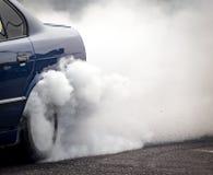 从汽车的轮子的下面烟 免版税库存照片