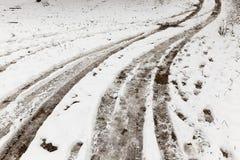 汽车的轮子的踪影在用雪盖的一条农村路的 库存照片