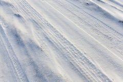 汽车的轮子的踪影在积雪的路的 免版税库存图片