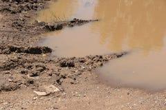 汽车的轮胎轨道是在沙子上的另一边的去的thouhgh和土一个泥泞的水坑的看法的关闭 免版税图库摄影