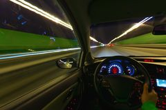 汽车的运动在国家高速公路的晚上高速从里面的观察与司机 手 免版税库存图片