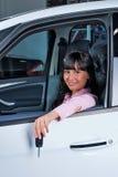 汽车的年轻愉快的妇女有钥匙的在手中 免版税图库摄影