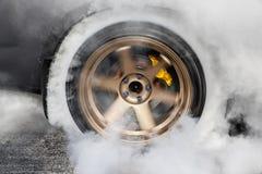 汽车短程加速赛汽车为准备种族烧轮胎 库存照片