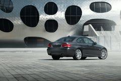 汽车站立在铺石空的停车场的BMW小轿车E92在现代大厦附近在白天 免版税库存照片