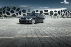 汽车站立在铺石空的停车场的BMW小轿车E92在现代大厦附近在白天 免版税库存图片