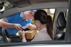 汽车签署的署名的妇女在接受包裹的巧妙的电话 图库摄影