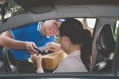 汽车签署的署名的妇女在接受包裹的巧妙的电话 库存照片