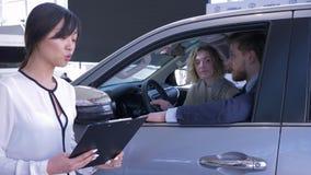 汽车经销商亚裔妇女画象咨询坐在汽车沙龙的客户年轻配偶,当买家庭汽车在时 股票录像