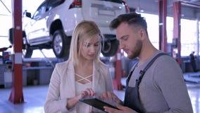 汽车维修车间,有数字片剂的技工谈话与汽车背景的女性客户在液压悬挂的 股票录像