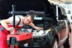 汽车维修车间-工作者检查并且调整a车灯  库存照片
