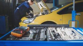 汽车自动电子-技工修理车松开汽车细节-车库服务 库存照片