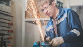 汽车自动车间-有一把圆锯的工作者男性白种人研的金属建筑,远距照相 库存图片