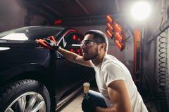 汽车详述-人拿着microfiber手中并且擦亮汽车 免版税库存照片
