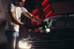 汽车详述-有轨道磨光器的人在汽车修理店 选择聚焦 免版税库存照片