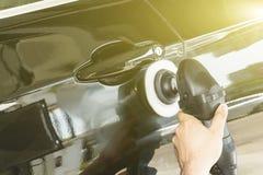 汽车详述-有轨道磨光器的手在汽车修理店 选择聚焦 免版税库存照片