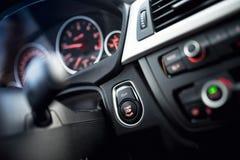 汽车起动和停止键 与仪表板和驾驶舱细节的现代汽车内部 免版税库存照片