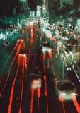 汽车车灯和尾灯在一条城市街道上在晚上 库存图片