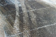 汽车轮子踪影在路的有泥和白色雪的 背景蓝色雪花白色冬天 库存照片